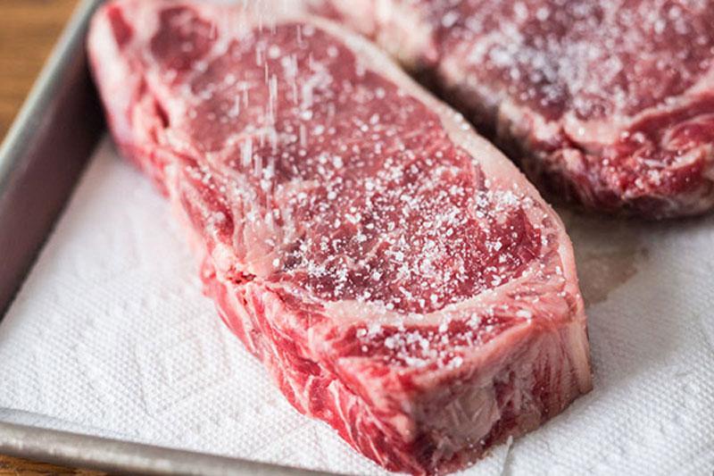 ướp muối vào thịt bò