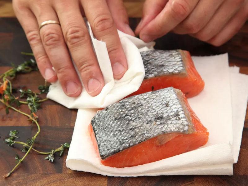 Dùng khăn giấy thấm khô bề mặt cá